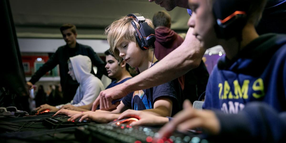 Tre tonåringar sitter med gaming-hörlurar  framför tangentbord, möss och datorer och spelar.