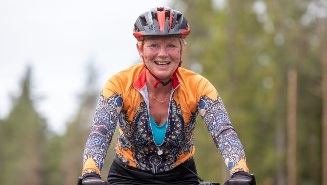 Kvinnlig cyklist med hjälm och färgglada kläder.