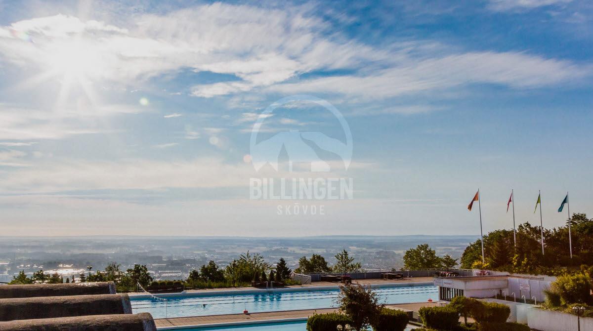 två simbassänger på Billingebadet, precis innan sluttningen nedanför syns staden och solen skiner på en blå himmel.
