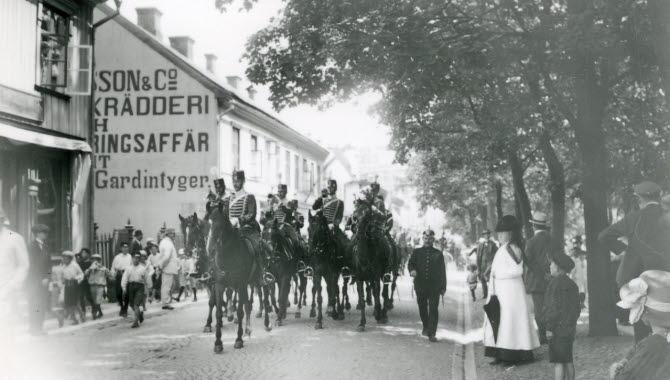 Fem husarer till häst rider fram utmed en kullerstensgata. På sidorna av gatan står människor och tittar på.