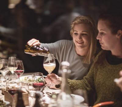 Två kvinnor äter middag på restaurang. Den ena häller upp dricka från en flaska till den andra.