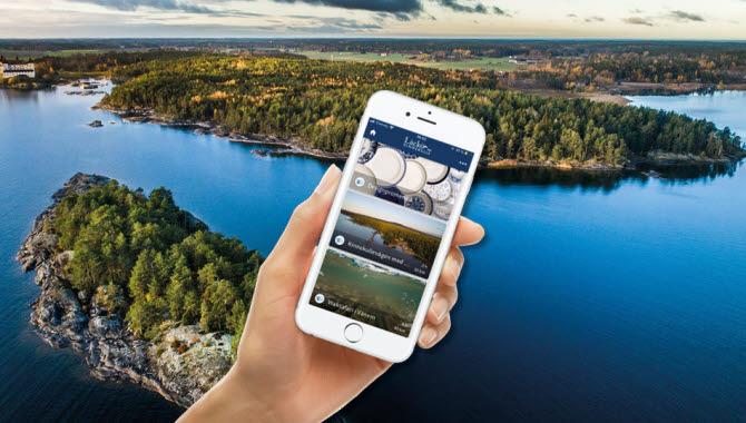 En hand som håller i en mobil framför en vy med skärgård