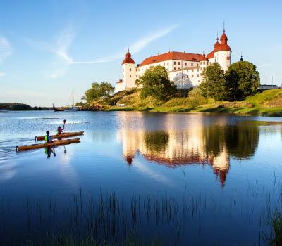 Par paddlar kajak utanför Läckö Slott