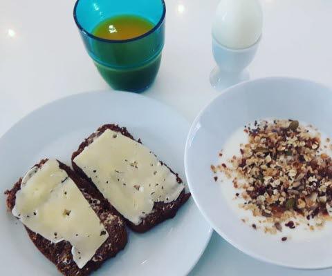 Frukost med två ostsmörgåsar, ett glas juice, ett kokt ägg och en tallrik med fil och flingor