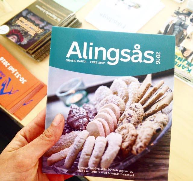 En hand håller fram Alingsås turistkarta