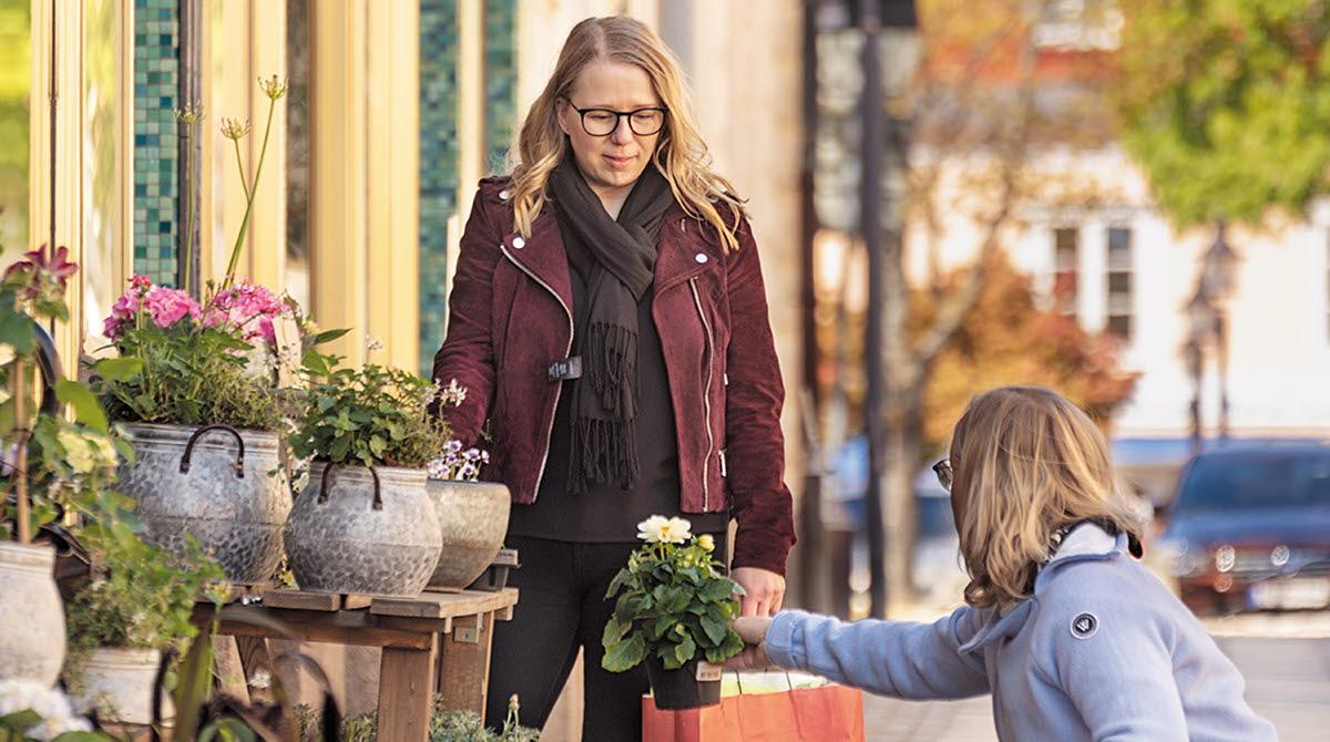 Två kvinnor tittar på blommor utanför butik.