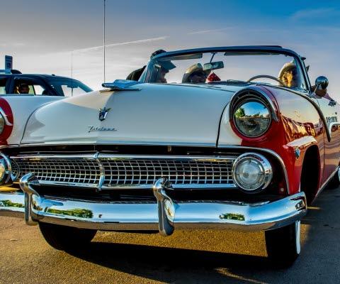 Fronten på en blänkande gammal amerikansk bil i rött och grått.
