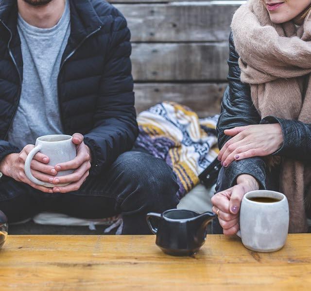 Två människor som sitter vid ett bord och dricker varsin mugg kaffe