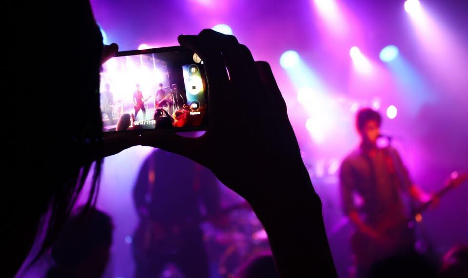 Person med mobilkamera filmar en konsert.