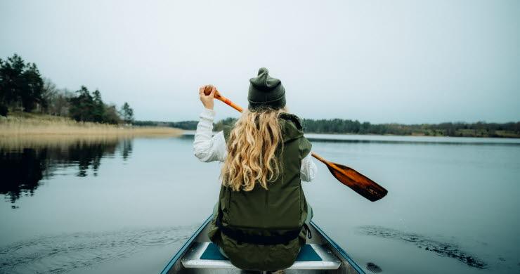 Kvinna paddlar kanot