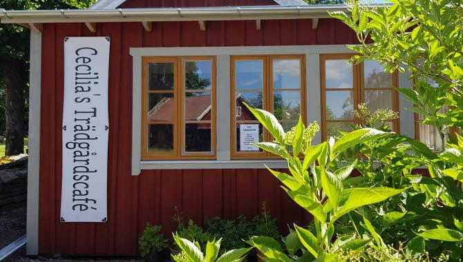 Rött hus med vita knutar omgivet av en grön blommande trädgård.