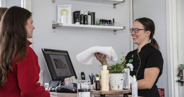 Två kvinnor vid en receptionsdisk ler mot varandra
