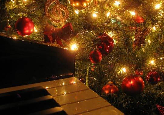 Julpyntad gran med en del av ett piano i förgrunden.