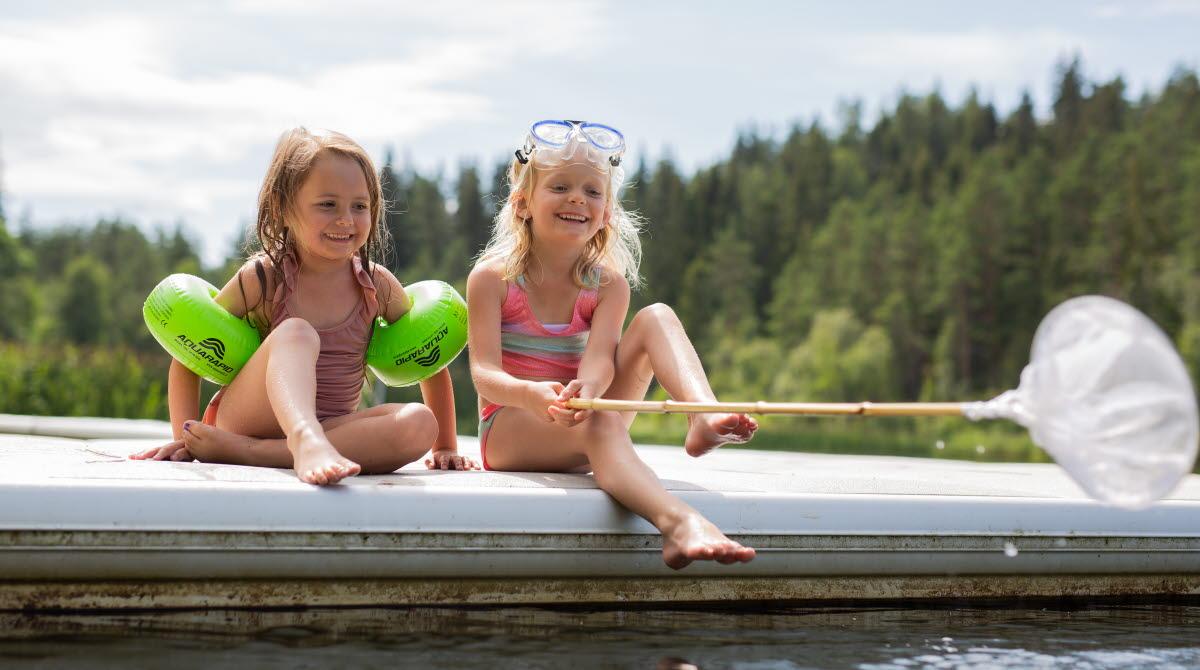 Barn badar på strand med brygga vid lilla havssjön