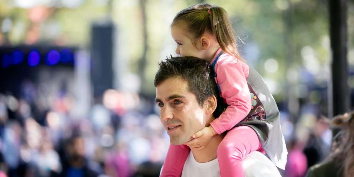 Pappa går genom festivalområde med sin dotter på sina axlar. I bakgrunden kan man ana en scen med ett publikhav framför.