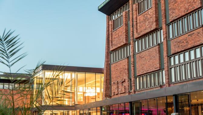 Skövde Kulturhus, ett hus i rött tegel med många fönster och flera reliefer.