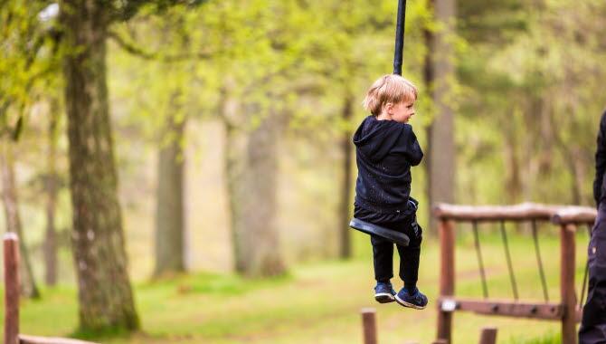 Ett barn åker linbana. I bakgrunden finns grönskande träd.