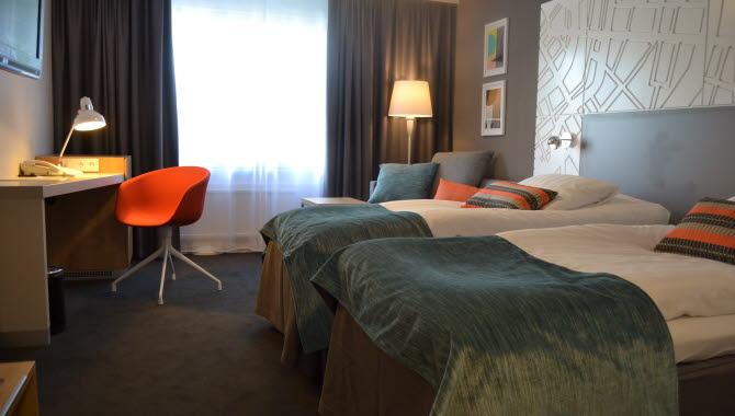 Två sängar med turkosa överkast står intill varandra inne på ett hotellrum. Framför sängar står även ett skrivbord med en orange stol.