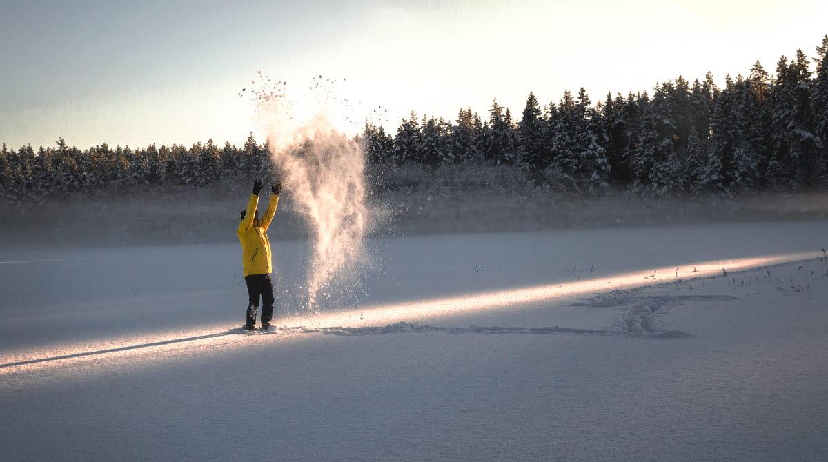 Man slänger upp snö som bildar ett hjärta i luften