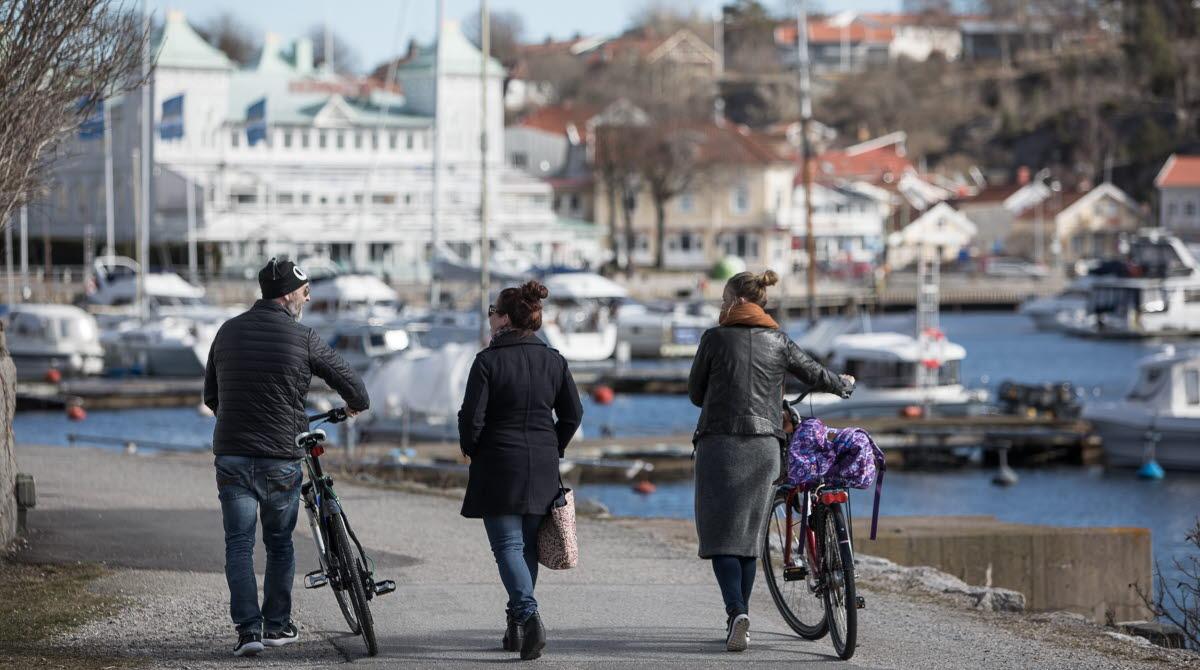 Tre personer promenerar i centrala Strömstad, vid Laholmen och gästhamnen.