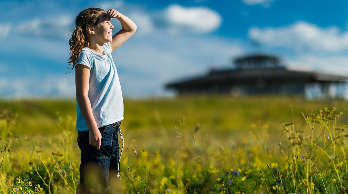 Girl standing on a meadow and peeking towards the sky. The view tower at Fågeludden is in the background.