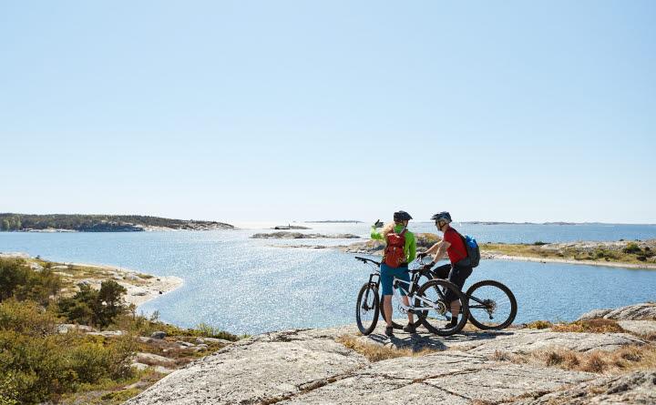 Två cyklister står uppe på ett berg och njuter av hänförande utsikt över en solig skärgård. Himlen är helt blå.