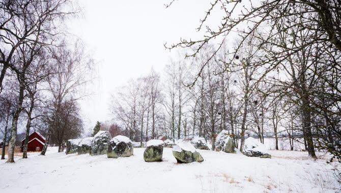 24 stenar ligger i formation som ett skepp. Askeberga skeppssättning i vinterskrud.