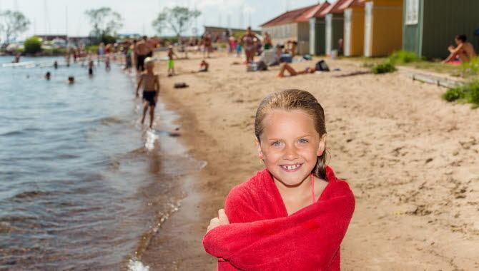 En flicka framför de karaktäristiska badhytterna vid  Hjobadet.
