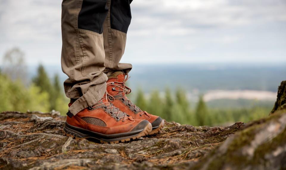Ben i röda skor ståendes på en klippa med utsikt över skog och vidder