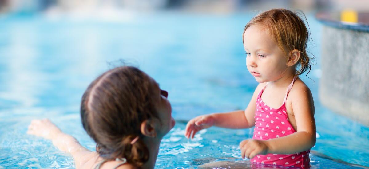 En mor och dotter i en simbassäng.
