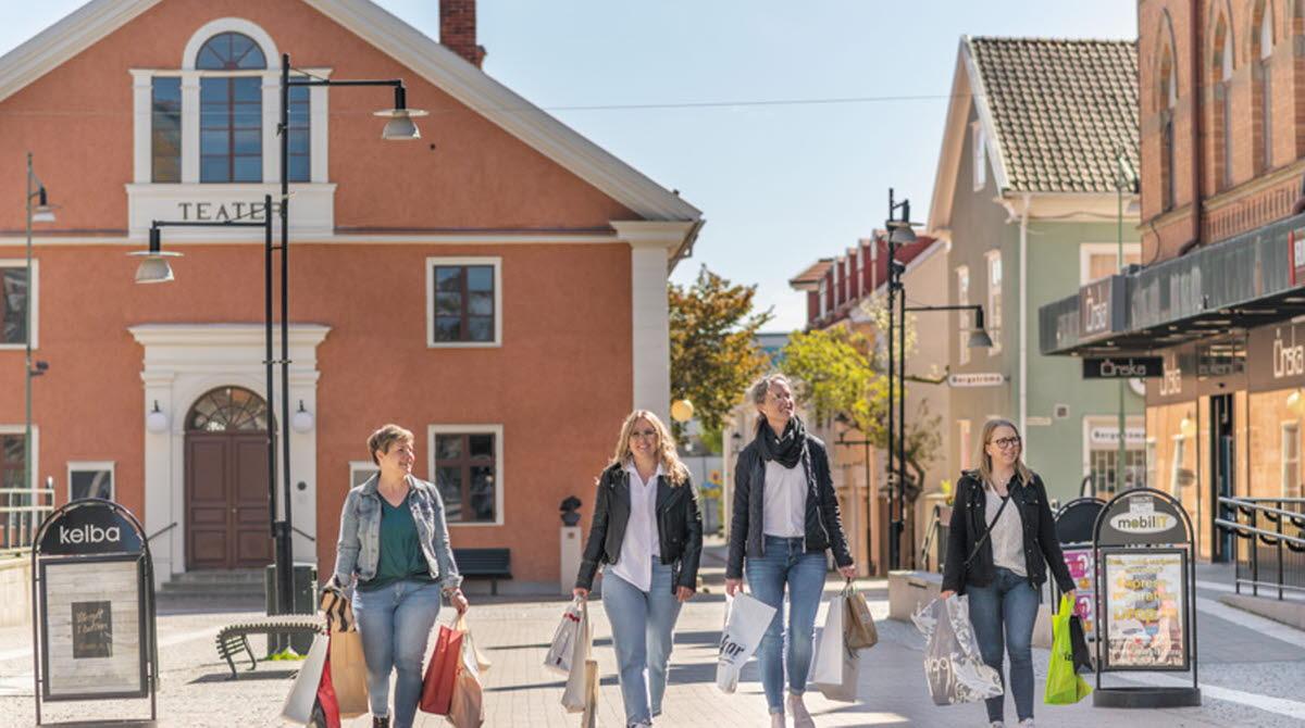 Fyra kvinnor går på gågatan i Mariestad. De har fyllda shoppingpåsar i händerna.