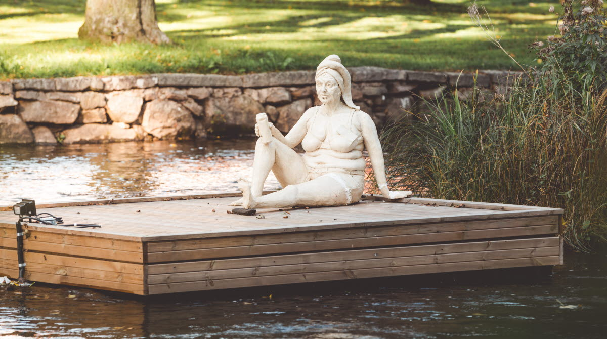 En skulptur av en kvinna Britt-Marie som sitter på en pråm i ån Tidan i Tidaholm.