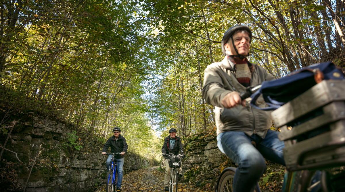 Tre män cyklar längs en banvall omgivna av höstfärgade blad.