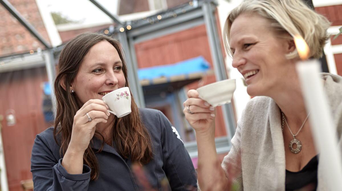 två kvinnor som sitter och dricker kaffe i ett växthus.