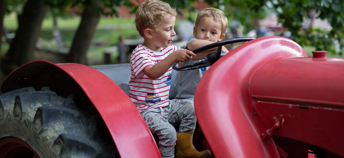 Två pojkar som sitter i en röd traktor.