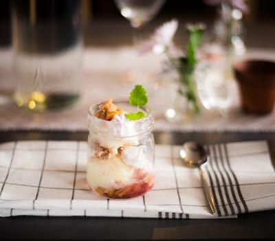 På en rutig kökshandduk står en glasburk dukad innehållandes en god blandning av glass, grädde, bär och nötter.