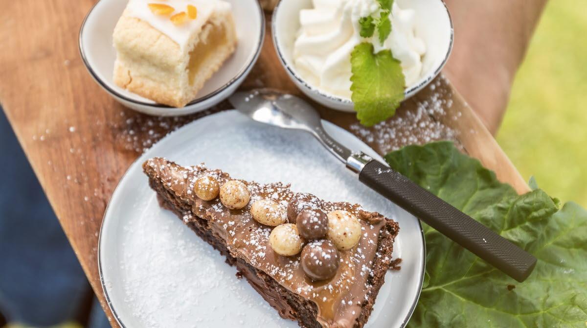 Kladdkaka, bulle och en kaka på en träbräda.
