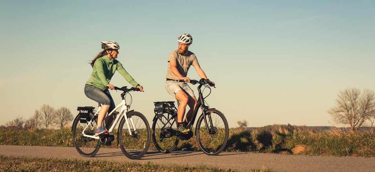 Par som cyklar på en grusväg.