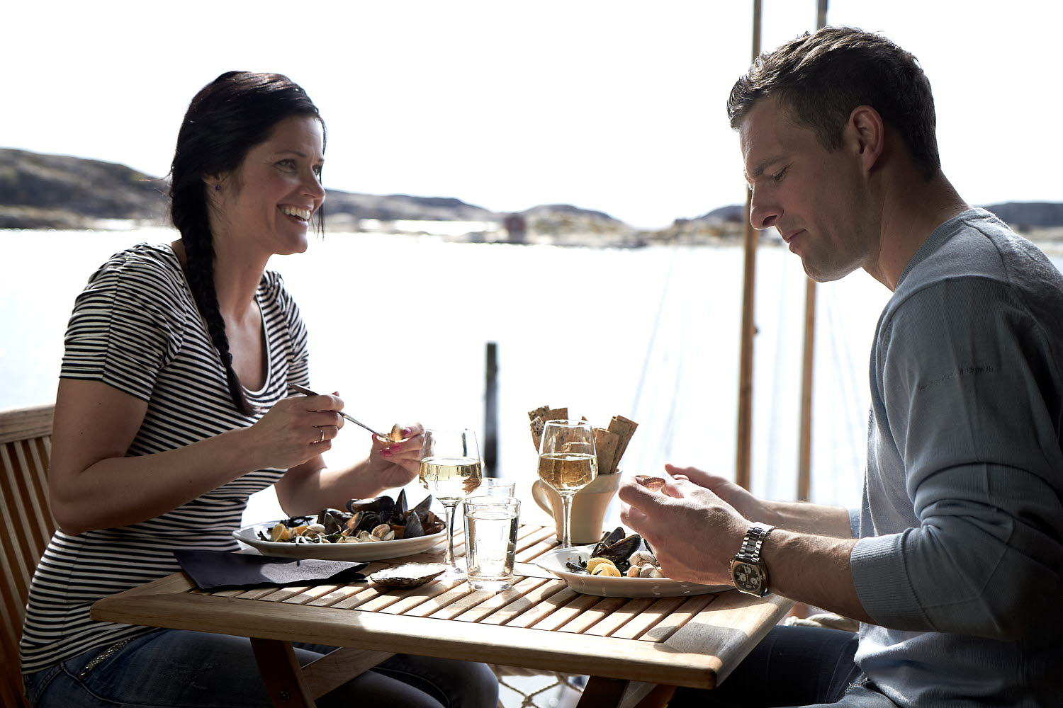 Couple eating mussel dinner by the sea - Photo Cred Jonas Ingman