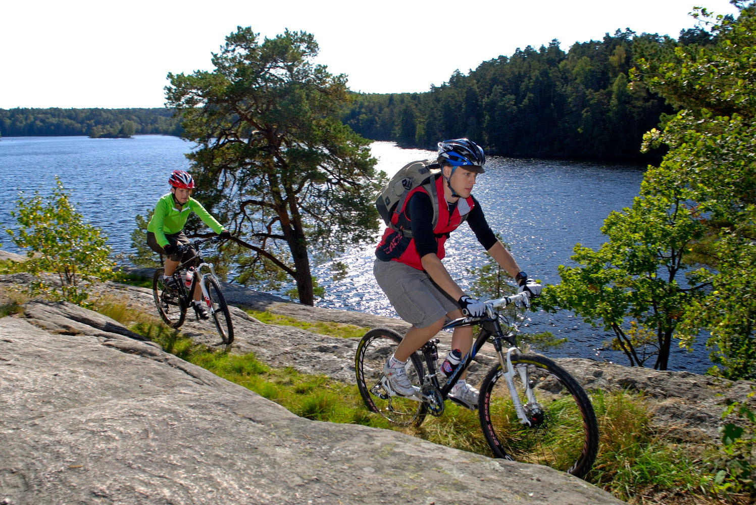 Couple mountain biking on the cliffs by a lake - Photo Göran Assner.jpg