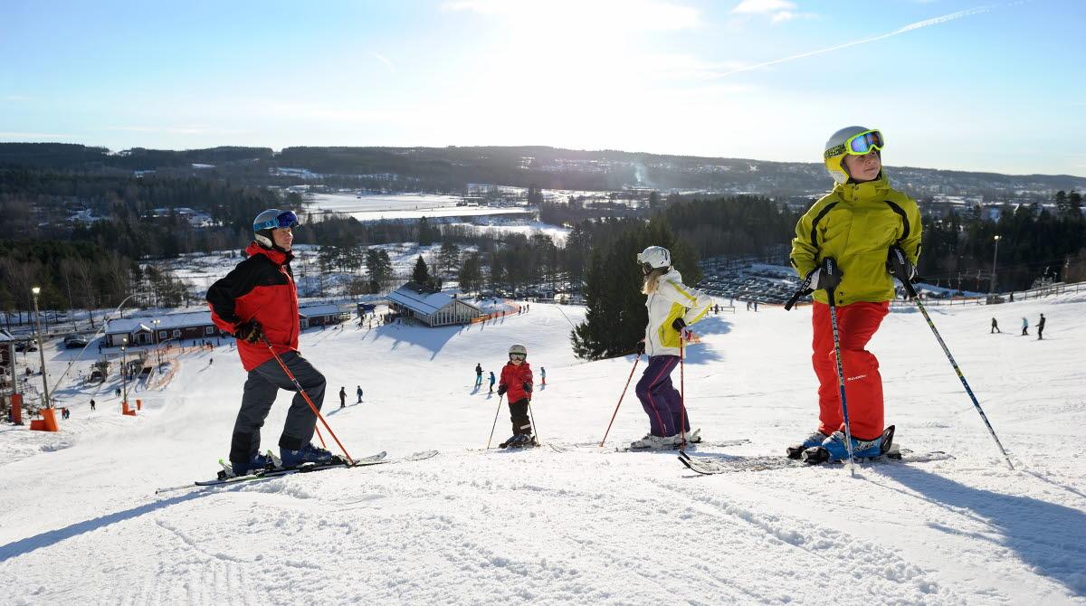 Fyra personer i färgglada skidkläder åker skidor i Ulricehamn ski center