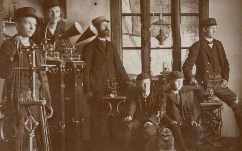 """Gammalt fotografi av sex män som blickar till höger. Används som affischbild för utställningen """"Teknik i nöd och lust""""."""