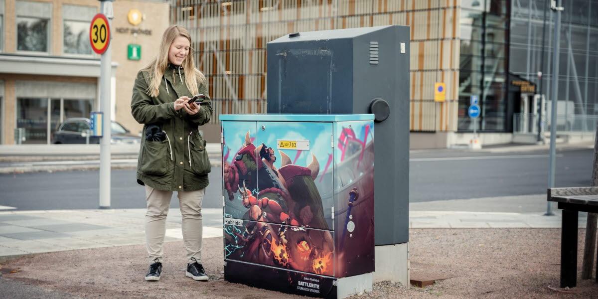 Kvinna i grön jacka och blont hår står med sin telefon i handen intill ett folierat elskåp som föreställer en spelkaraktär från spelet Battlerite.