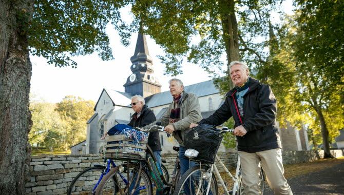 Tre män kommer gåendes och leder sina cyklar längs en stenmur. I bakgrunden ser man Varnhems klosterkyrka.