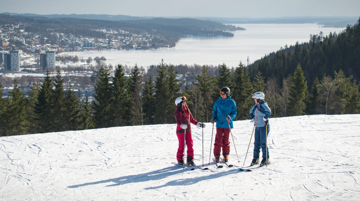 Three children in colorful clothes with skis on top of Ulricehamn Ski Center.