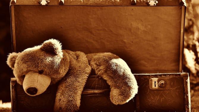 En teddybjörn ligger halvvägs nerstoppad i en gammaldags resväska. Hela bilden är sepia-tonad i brunt.