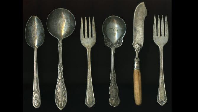 Sex stycken antika silverbestick ligger uppradade på ett svart underlag.