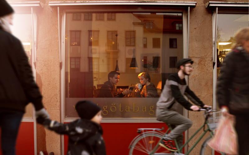 Ett par sitter och fikar och tittar medans folk går förbi.
