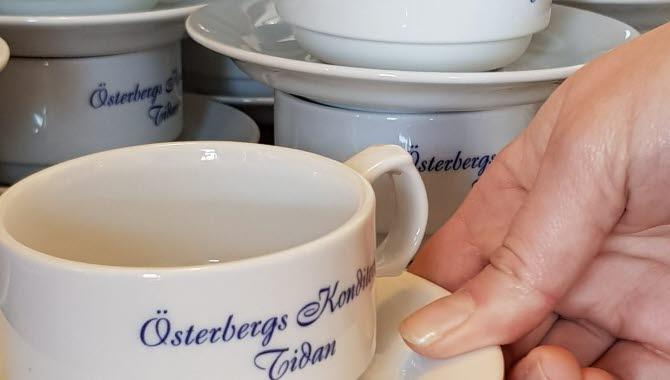 En hand lyfter en vit kopp med den snirkliga blå texten Österbergs Konditori Tidan