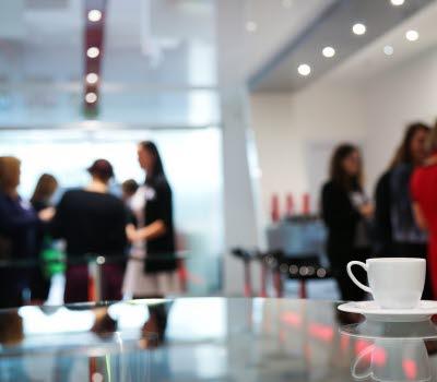 En kafferast vid en konferens. En kaffekopp står i förgrunden och några personer syns suddigt bakgrunden.